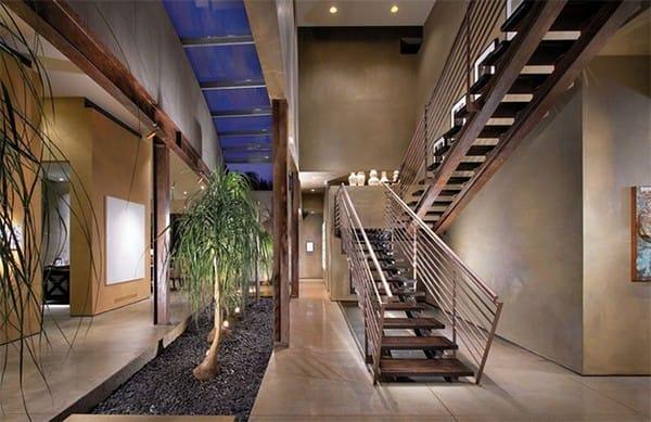 Thay vì thiết kế một hàng lang lờ mờ ánh đèn điện, gia chủ đã bố trí một khu vườn trải dài lối đi, với không gian kính trong suốt ở phía trên nối với bầu trời bao la.