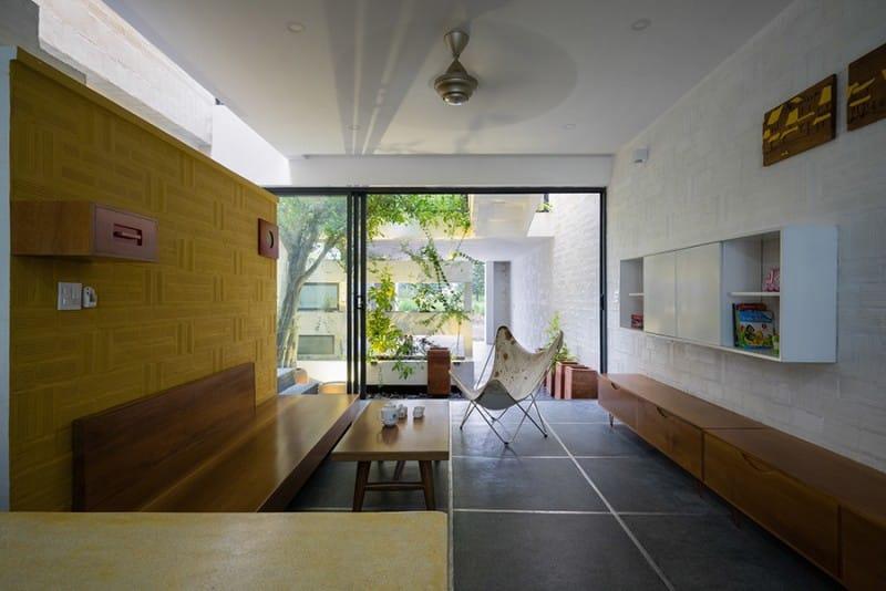 Thay cho cổng cao đóng kín là những bức vách hở kết hợp với cây xanh tạo nên sự kín đáo tương đối cho chủ nhà.