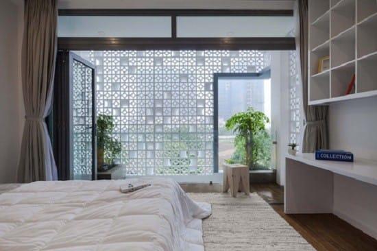 Phòng ngủ chính ở tầng 2 trở nên thoáng rộng và sáng sủa hơn nhờ lớp tường bê tông lỗ chắn.