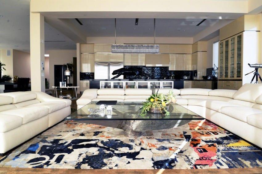 Đồ nội thất trong phòng bao gồm cả sàn gỗ, thảm nhiều màu sắc hòa hợp ghế sofa kem.
