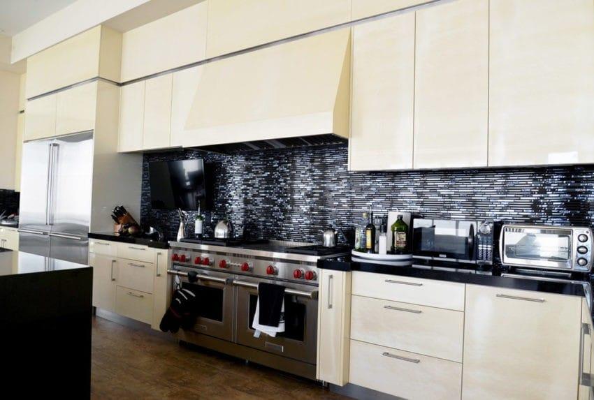 Phòng bếp dùng hai gam màu chủ đạo là đen và trắng, từ một bộ bàn ăn gỗ đen kết hợp với tường bếp lát đá đen cùng bộ tủ bếp sáng bóng sang trọng. Sử dụng một vài đồ bếp đen đi cùng với sắc trắng khiến căn bếp có không gian thoáng và sáng. Cùng với đó, việc lựa chọn thêm đồ gỗ cũng giúp không gian bớt bị lạnh và nhàm chán.