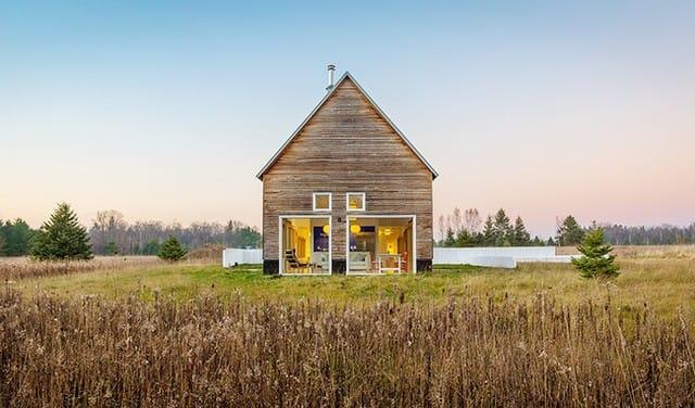 Nhìn từ xa, ngôi nhà cấp 4 rộng khang trang với tường ốp gỗ ấm áp, những ô cửa hình vuông được lắp đặt chất liệu kính trong suốt tạo sự hài hòa giữa thiên nhiên bên ngoài với các khu vực chức năng bên trong.
