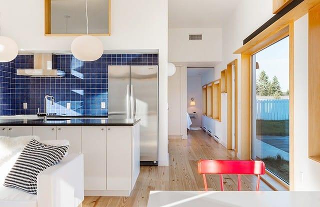 Không gian nấu nướng được bố trí ngay khoảng diện tích phía sau sofa. Dù ngôi nhà được xây dựng với diện tích khá rộng nhưng mọi khu vực chức năng đều được sắp đặt quy củ để mọi người dễ dàng cảm nhận được sự thông thoáng và thoải mái. Góc bếp được thiết kế đơn giản với hệ thống tủ bếp màu trắng, làm nền cho gạch ốp tường màu xanh biển đậm toát lên vẻ đẹp thanh lịch, hiện đại cho khu vực này.