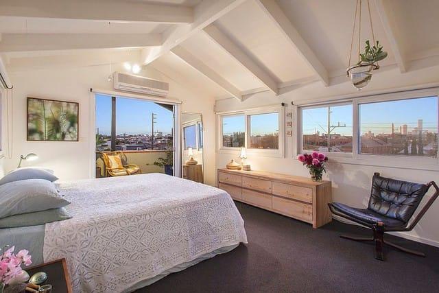 Phòng ngủ yên tĩnh và hiện đại với sắc trắng bao trùm, phóng ra xa là cảnh quan rộng lớn của thành phố Melbourne.