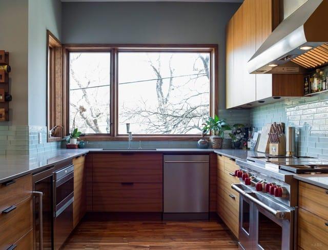 Phía bên kia của nhà bếp được gắn tủ và máy hút mùi. Có cửa sổ để ánh sáng tự nhiên chiếu vào.