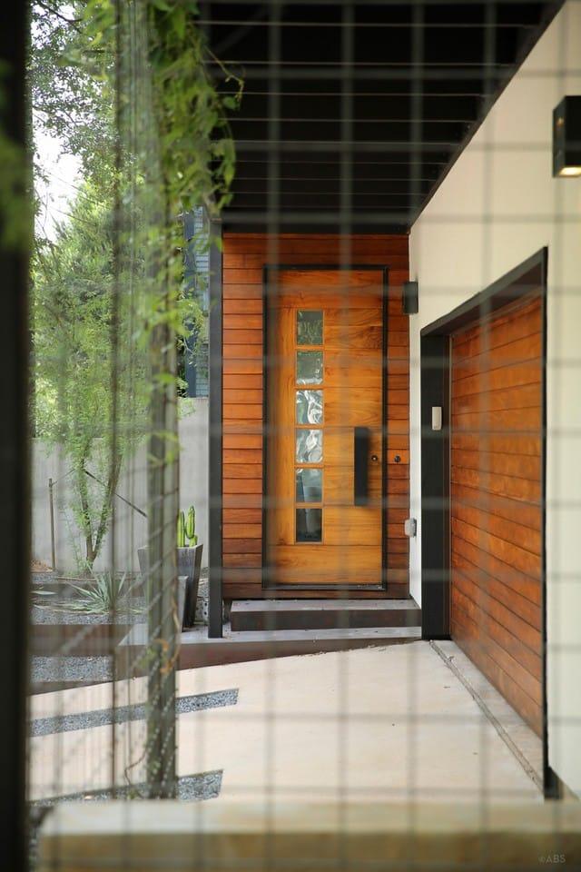 Cánh cửa được thiết kế kết hợp gỗ và thép, có lắp đặt một hệ thống khóa công nghệ cao. KTS đã thiết kế lối vào ở ngay bên cạnh nhà để xe.