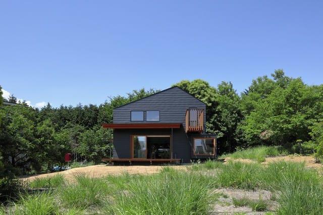 Ngôi nhà gỗ xinh xắn nằm ở vùng nông thôn tỉnh Yamanashi, Nhật Bản. Nhìn từ bên ngoài, người ta có thể thấy rõ kiến trúc độc đáo với phần mái hiên rộng, cửa lớn và ban công gỗ dẫn ra từ tầng lửng.