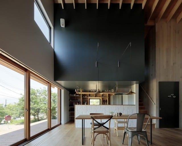 Cửa kính lớn ở tầng một giúp người ngồi trong nhà vẫn có thể ngắm toàn vẹn không gian bên ngoài. Mái hiên rộng vừa có tác dụng đỡ hắt nắng vào trong, vừa là chỗ râm mát có thể ngồi hóng gió, thư giãn. Khu vực bếp, phòng ăn được bố trí ngay gần cửa ra vào.